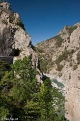 Tief unten in der Schlucht fließt der wilde Fluss Guil mit seinem türkisfarbenen Wasser, links verschwindet die Straße in einem schmalen Tunnel