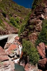Meist verläuft der Fluss Cians direkt neben der Straße, teilweise bildet er dort in dem roten Gestein auch kleine Wasserfälle