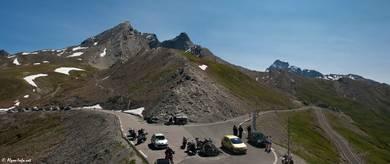 Der Scheitelpunkt des Col Agnel mit seinem kleinen Parkplatz und dem Grenzstein, im Hintergrund von links nach rechts die Gipfel des Pain de Sucre, des Pic d'Asti und des Monte Viso