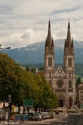 Blick durch die Straßen Voiron Richtung Kirche, im Hintergrund die ersten höheren Berge der Alpen